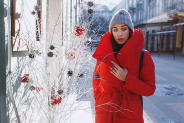 beautiful woman staying near tradidional christmas tree wear warm red down jacket.  Christmas, new year and winter holiday concept