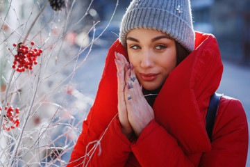 stunning girl in grey knitted hat and red coat smiling while she stands on the street before Christmas decorations in a sunny winter day. Christmas, new year and winter holiday concept - Image
