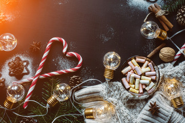 Christmas decor. Chocolate or cocoa with marshmallow, cookies, candy and the garland on a dark background with warm rays of the sun.