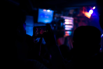 Silhouette of hands using smart phone to take pictures and videos at live concert; Smartphone records live music; Take photo in front concert stage