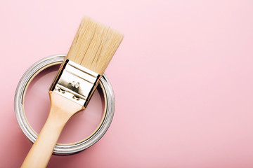 Brush with wooden handle on open can of pink paint on pastel background. Renovation concept. Macro. Wall mural