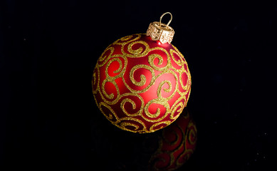 Pick decor for christmas tree. Christmas ornament single red ball on black background. Christmas ornament concept. Elegant and luxury christmas decor close up. Ball ornament on black surface