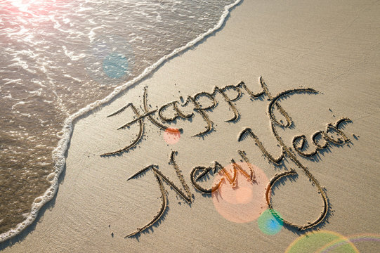 Happy New Year message handwritten in smooth sand with sunrise lens flare over oncoming wave on the beach