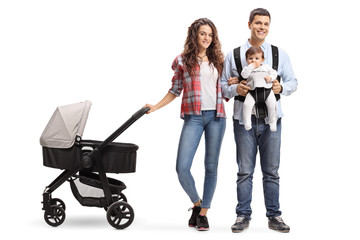 Young mother with a stroller and a father with a baby in a carrier