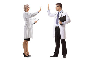Male and female doctor gesturing high-five