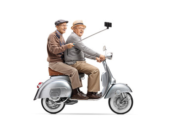 Two senior men riding on a vintage scooter taking a selfie with a stick