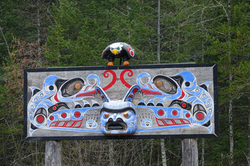 Colorful wooden totem pole is well preserved near a remote forest in Canada.