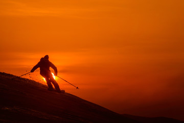 SILHOUETTE: Unrecognizable skier shredding the fresh untouched snow at sunset.
