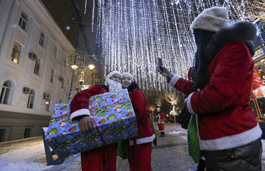 People dressed as Santa Claus take a picture next to the Christmas illuminations in Almaty
