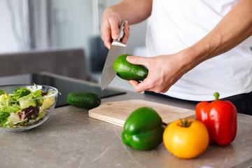 Handsome young man at kitchen at home cooking vegetables make salad.