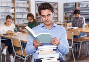Portrait of focused man browsing books