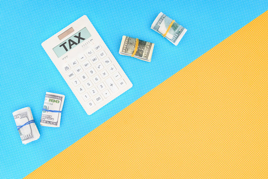 top view of calculator with word 'tax' and money rolls on blue and yellow background