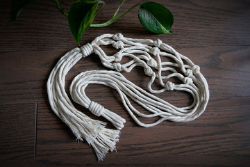 A hand made natural cotton macrame plant hanger laying on a wooden floor.
