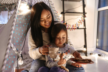 Photo of relaxed asian family mother and daughter eating cookies, while resting together at home in children playing tent