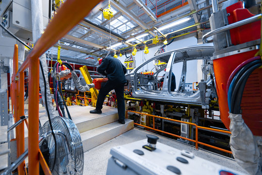 Engineer assemble the car on the production line. Car manufacturing plant