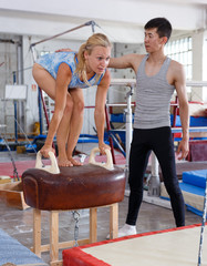 Man and woman training on pommel horse