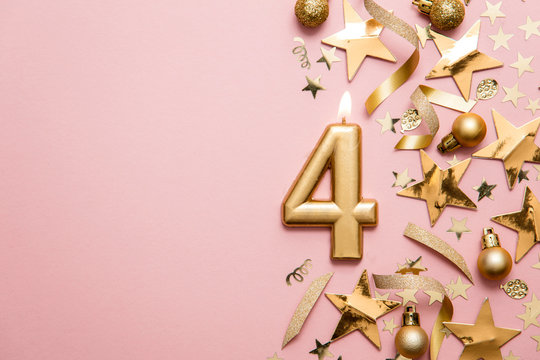Number 4 gold celebration candle on star and glitter background