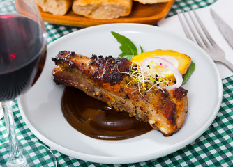 Baked under a mustard sauce tasty pork ribs with spicy sauce