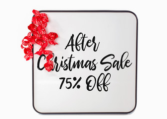 after Christmas sale sign with red curly ribbon on white dry erase board
