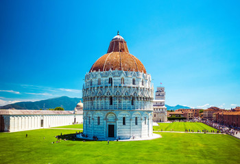 Baptistery of St. John on Square of Miracles, Leaning Tower, famous inclined tower of Pisa with green lawn in Pisa, Tuscany, Italy