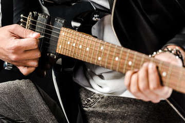 partial view of male rock musician in leather jacket playing on electric guitar isolated on white