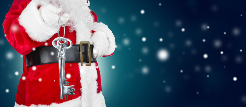 Santa Claus with home key on winter background