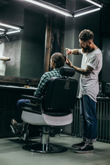 Full length of experienced barber doing haircut for his client