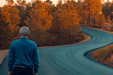 Active senior man stands alone on lonely road between mountains