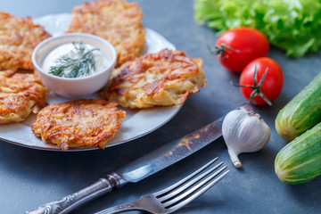 Draniki - potato fritters. potato pancakes lie on a plate. The national dish of Belarus, Ukraine, Russia.