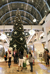 People take photos near the Christmas tree, displayed in the Mall of Emirates in Dubai