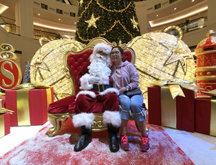 A woman takes a photo with Santa Claus in the Mall of Emirates in Dubai