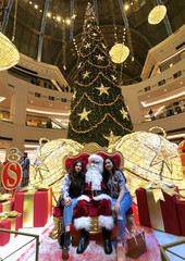 People take photo with Santa Claus in the Mall of Emirates in Dubai