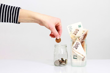 hand putting some money into a glass jar