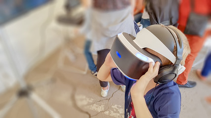 Kid in formal outfit wearing VR glasses putting hands out in excitement