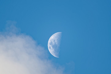 zoom to the moon during the day a cloud is going through