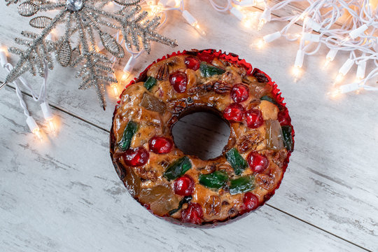 whole fruit cake with Christmas star and lights flat lay