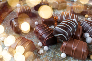 Chocolate candy with drizzle stripes on vintage tray with bokeh lights