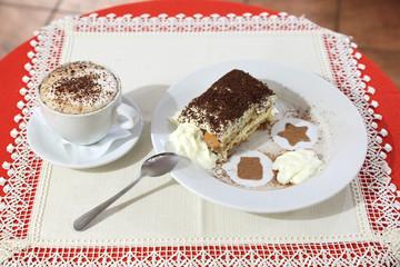 Tiramisu z kawą cappucino na stoliku.
