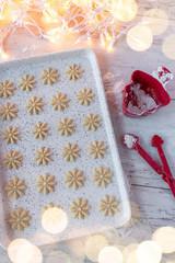 Raw dough Christmas sugar cookies pressed shapes on baking sheet flat lay