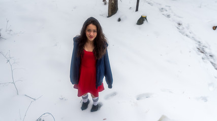 Young Asian teen in red dress surrounded by snow