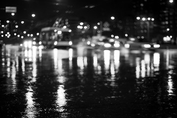 Rainy city road at night. Defocused black and white image