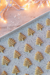 Raw dough Christmas sugar cookies pressed shapes on baking sheet flat lay
