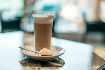 A cup of hot latte coffee in transparent glass on white plate with a sweet treat and teaspoon a glass table with light bokeh background, front view.