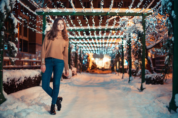 Pretty dark haired girl wearing blue jeans and beige top with snowflakes Christmas lights outdoor at night time.