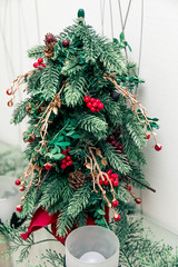 A Christmas tree decorated with red berries and golden beads, ornaments. Artificial branches and pine cones. Merry Christmas and Happy New Year. Interior decor.