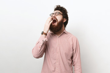 Bearded attractive man with messy hair, wearing gasses, feeling tired and yawning, covering nouth with hand