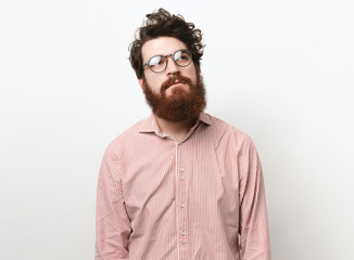 Unsatisfated bearded man with curly hair, wearing glasses and looking up