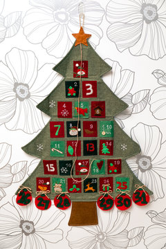 Handmade advent January calendar with numbers and pockets a shape of pine tree hanging on a white wall.