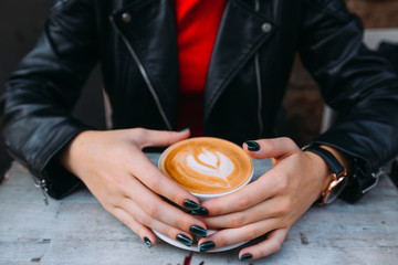 girl's hands with freckles around a cup of coffee. hot Cappuccin