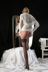 Frau in Strümpfen vorm Spiegel